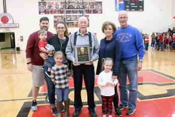 Ray Seeley holds the plaque that will be displayed in the lobby of Hilliard's gymnasium. He is joined by family members after Coach Tara Franklin announced his retirement Saturday evening.