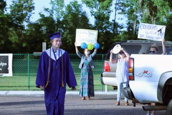Sonshine Christian Academy held commencement at Crossroads Family Worship Center May 17. Around 20 people attended the ceremony due to social distancing. Afterward, educators and friends held up congratulatory messages outside.