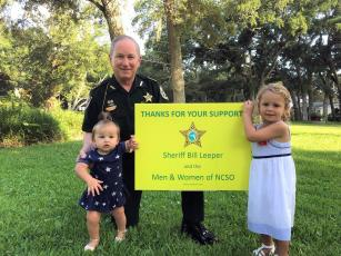 Sheriff Bill Leeper and granddaughters Memphis and Harper pose next to a Nassau County Sheriff's  Office sign. About 100 signs are available to thank those working during the pandemic. To obtain a sign signaling the NCSO stands with you, email aaspicer@nassauso.com.