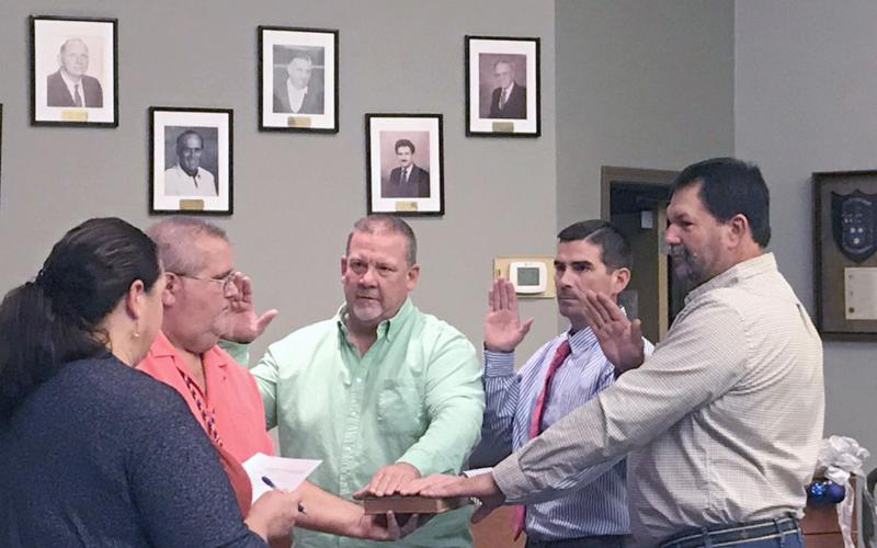 Hilliard town councilmen Kenny Sims, Jared Wollitz and Lee Pickett take the oath of office as Town Clerk Lisa Purvis officiates while Council President John Beasley holds a Bible.